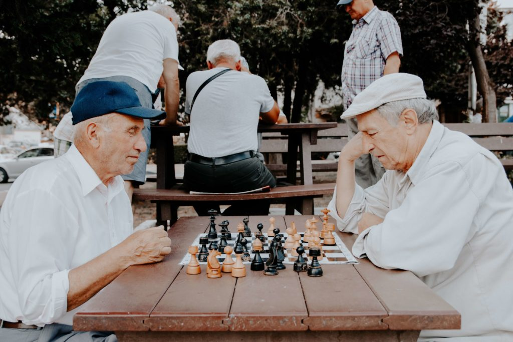 senior men playing chess outside